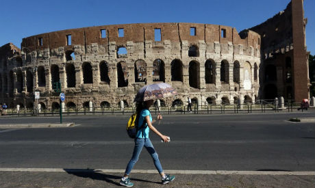 A woman walks past the ancient Colosseum, downtown Rome, Italy (Reuters)