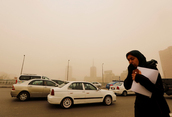 A woman covers her face as she walks on the 6th October Bridge during a sandstorm in Cairo, Egypt Ja