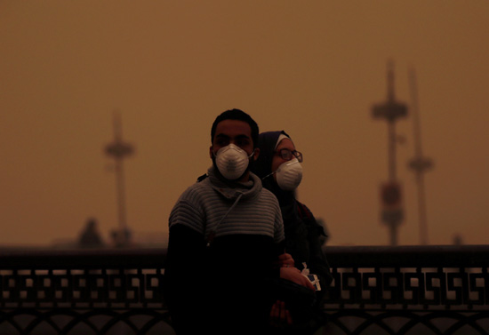 A couple covers their faces with masks during a sandstorm in Cairo, Egypt January 16, 2019. REUTERS