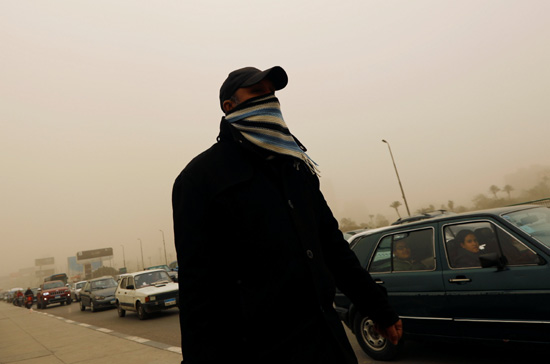 A man covers his face during a sandstorm in Cairo, Egypt January 16, 2019. REUTERS