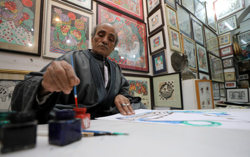 Artist, Hassan el-Shark, paints a piece of art with his own handcrafted colours, at his gallery in M