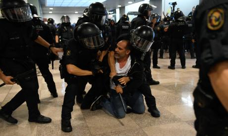Catalan regional police grab a protester at El Prat airport