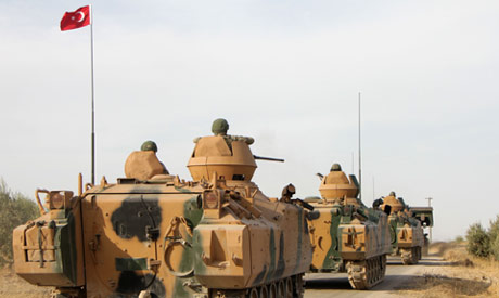 Turkish soldiers are trasported in armoured personnel carriers through the town of Tukhar, north of