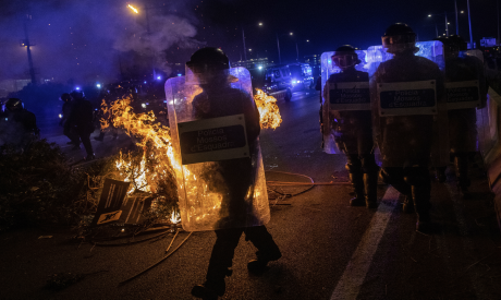 Riot police units walk past a barricade on fire