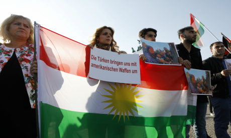 Protesters hold pictures and Kurdish flags during a rally against the Turkish military operation in