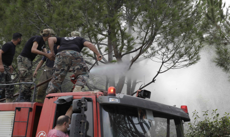 Firefighters extinguish flames after fires broke out around the village of Meshref