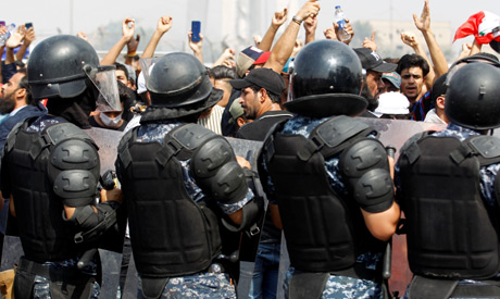 Iraqi security forces stand guard as demonstrators take part in a protest over unemployment, corrupt