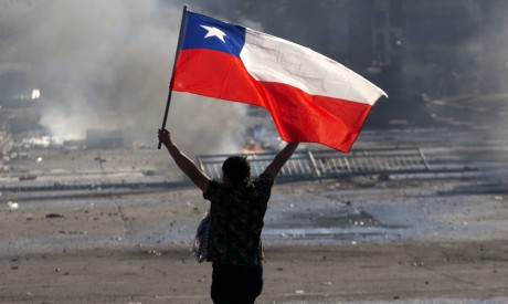 A demonstrator flutters a Chilean national flag during clashes with riot police