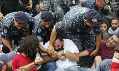 Lebanese riot policemen remove anti-government protesters who are holding each other
