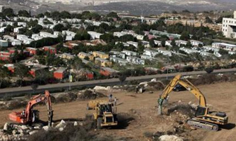 Construction vehicles prepare the ground as building of a housing project resumes in the West Bank J
