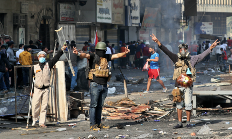 Anti-government protesters flash the victory sign while Iraqi security forces fire tear gas