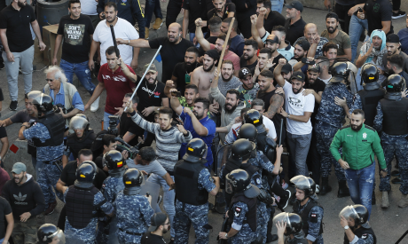 Riot police try to stop supporters of the Shiite Hezbollah group who arrived to burn and destroy ten