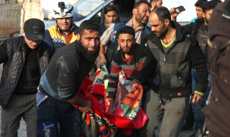 Residents and a rescue worker carry the body of a man killed in a reported Russian air strike
