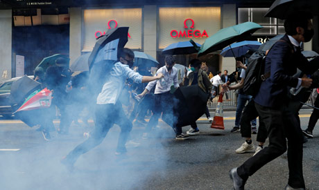 Office workers run away from tear gas as they attend a flash mob anti-government protest at the fina