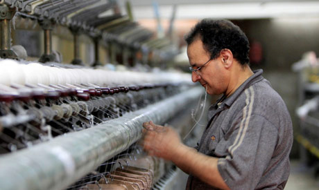 FILE PHOTO: A labourer works at a textile mill in Al-Mahalla al-Kubra, about 110 km north of Cairo M