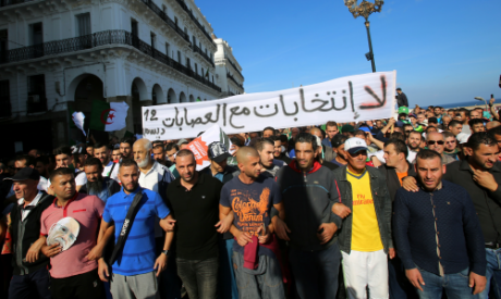 Demonstrators shout slogans and carry national flags during a protest in Algiers