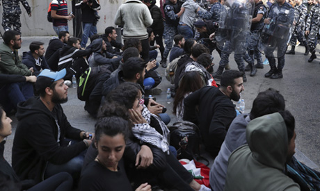 Riot police remove anti-government protesters blocking a road in Beirut, Lebanon, Monday, Nov. 25, 2