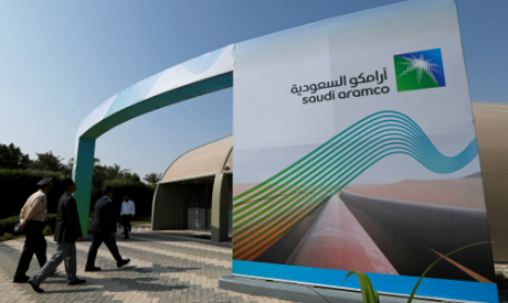 The logo of Aramco is seen as security personnel walk