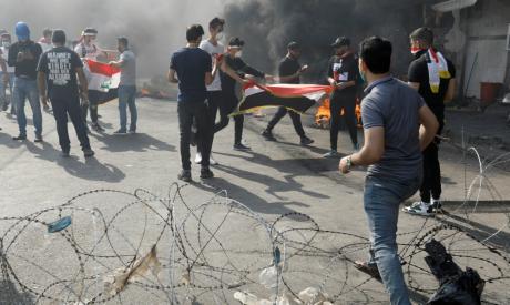 Iraqi demonstrators burn tires as they block the road