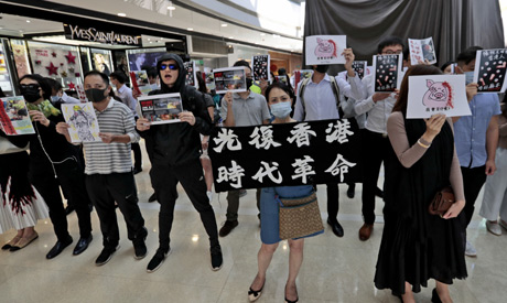 People shout slogans as they hold posters during a rally at a shopping mall in Hong Kong, Monday, No