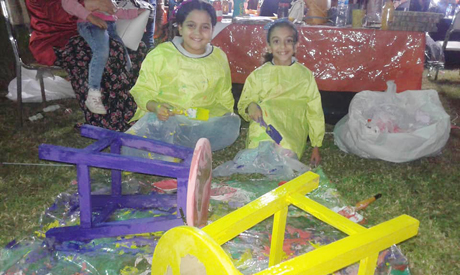 Sarah and Rahaf colouring wooden chairs