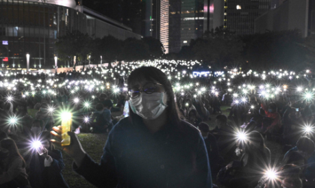 People light their mobile phones during a prayer rally