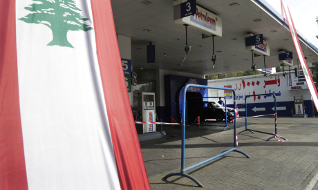 A Lebanese national flag hangs in front of a closed petrol station