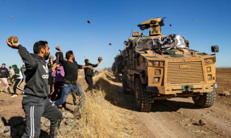 Kurdish demonstrators hurl rocks at a Turkish military vehicle