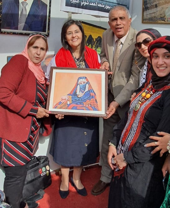 Dean of the Faculty of Information Howeida Mustafa carries a painting on show at Egypt