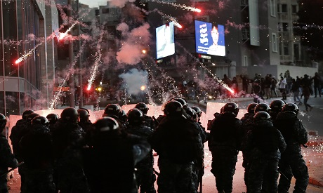 Lebanese riot policemen react to firecrackers that fired by the supporters of the Shiite Hezbollah a