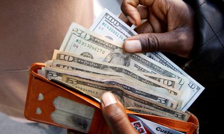FILE PHOTO: A man displays US dollar (Reuters)