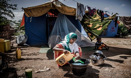 A displaced woman washes some dishes and utensils in front of her tent at a displacement camp in Bel
