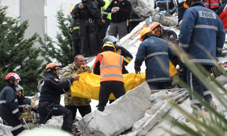 Rescue teams and firefighters carry the body of a victim