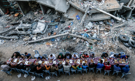Palestinian families break their fast next to a destroyed building