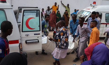 Somali men help to unload a victim, that was injured during a car bombing attack, at the Madina Hosp