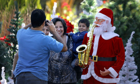 File photo: An Egyptian family pose for a photograph near Christmas trees and a Santa Claus mannequi
