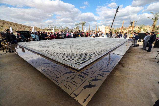 People gather around a depiction of the ancient Egyptian Pharaoh Tutankhamun