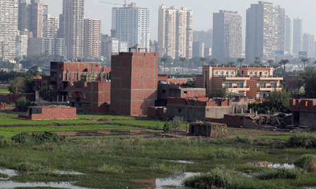 A view of houses and farmland on an island on the River Nile in front of high-rise buildings in Cair