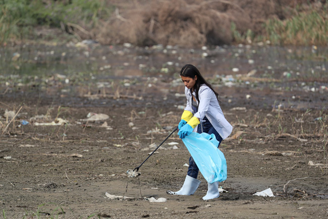 Actor Mai El Gheity collects waste and plastic as part of a campaign to clean up the river Nile by t