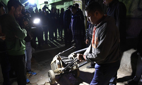 An Egyptian police officer in plainclothes rolls a piece of equipment to the site where the body of