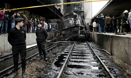 Policemen stand guard in front of a damaged train inside Ramsis train station in Cairo, Egypt (AP)