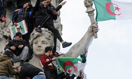 Protestors hold Algerian flags as they attend a demonstration against President Abdelaziz Bouteflika