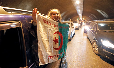 People celebrate on the streets after President Abdelaziz Bouteflika announced he will not run for a