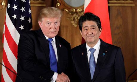 U.S. President Donald Trump, left, shakes hands with Shinzo Abe, Japan