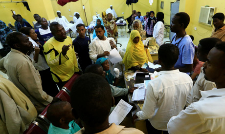 Relatives of victims of violence in the crackdown on Sudanese protesters listen to a doctor inside a