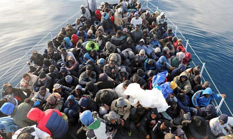 Migrants are seen in a boat as they are rescued by Libyan coast guards in the Mediterranean Sea off