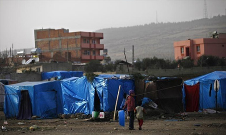 Syrian refugee children walk outside their tents in the southeastern city of Kilis, near the Syrian-
