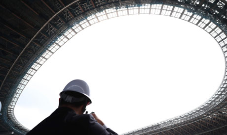 A member of the media looks at the new National Stadium under construction, a venue for the upcoming