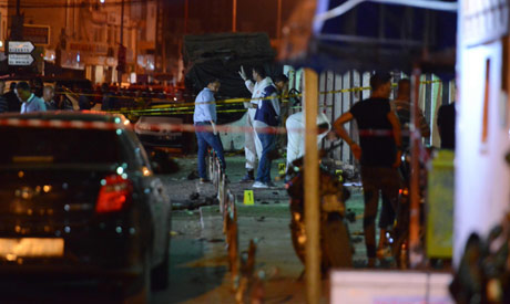 Tunisian explosive experts and security forces inspect the scene outside a metro station near the bu