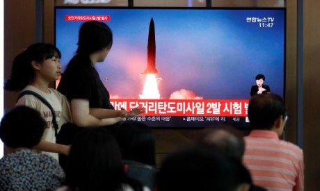 People watch a TV that shows a file picture of a North Korean missile for a news report on North Kor